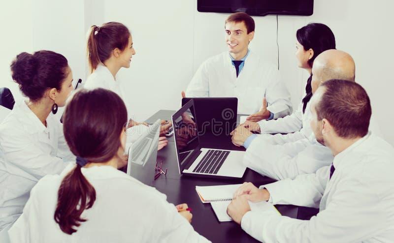 Wetenschapper die rapport voorleggen tijdens werkende vergadering stock afbeelding