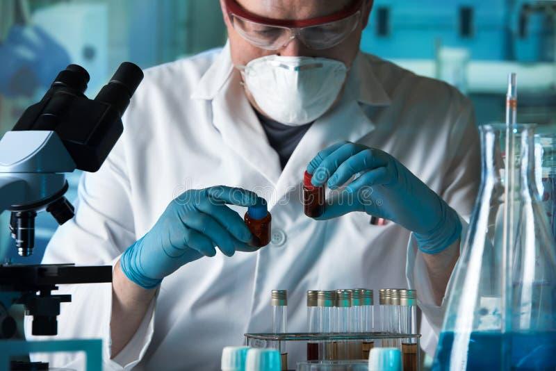 Wetenschapper die twee buizen in het laboratorium houden stock afbeeldingen