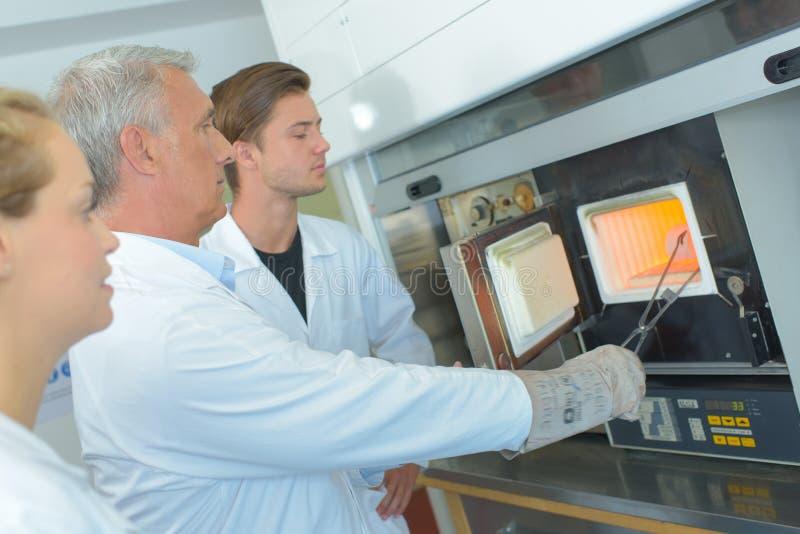 Wetenschapper die voorwerp verwijderen uit oven met tang stock foto