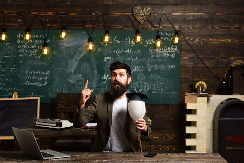 Wetenschapper hipster met lightbulb op bord De gebaarde bol van de mensengreep in klaslokaal Zakenman in kostuum bij schoolbank stock afbeelding