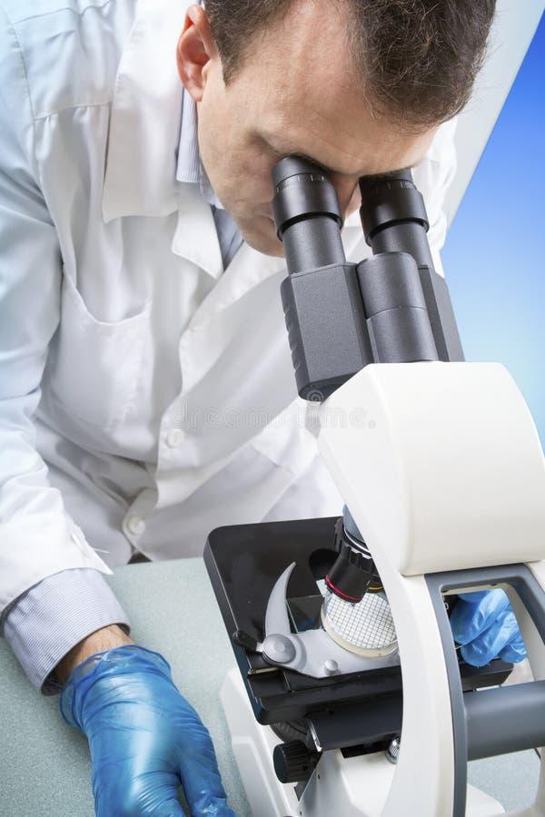 Wetenschapper Looking Through Microscope in Laboratorium stock afbeeldingen