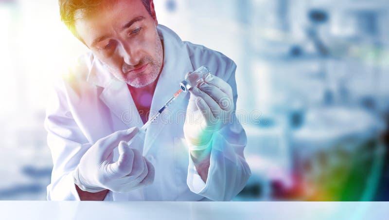 Wetenschapper met spuit en flesje in handen achter een lijst stock foto's