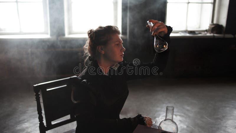 Wetenschapperonderzoeker met een fles radioactief materiaal De studie van radioactiviteit royalty-vrije stock fotografie