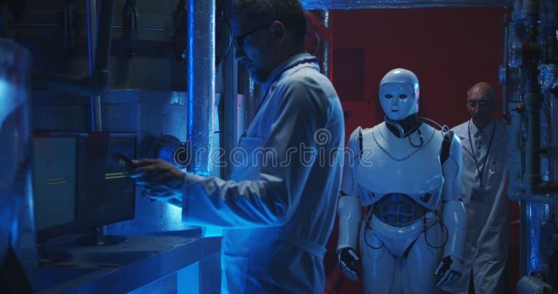 Wetenschappers die humanoidrobot testen stock foto's