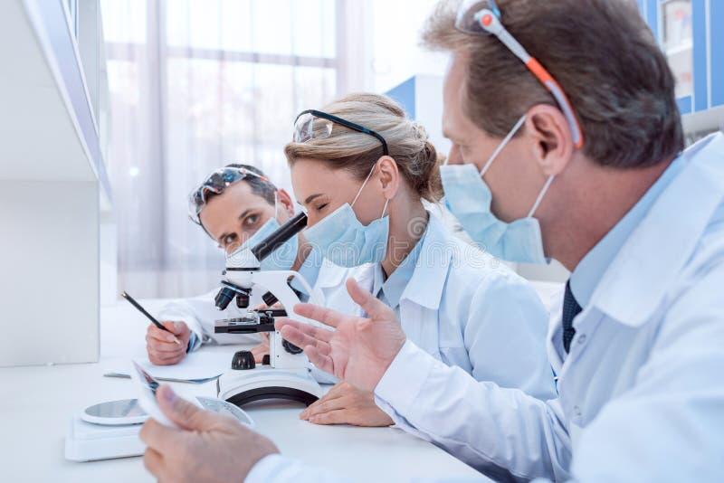 Wetenschappers die microscoopanalyse maken stock fotografie
