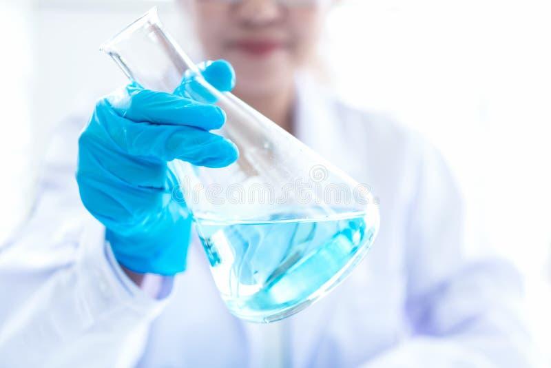 Wetenschappers die studiegegevens analyseren en microscoop evalueren Gezondheidszorgonderzoekers die wat onderzoek met druppelbui stock afbeelding