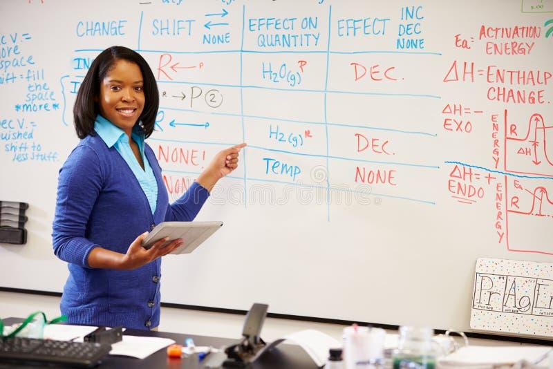 Wetenschapsleraar Standing At Whiteboard met Digitale Tablet stock afbeeldingen