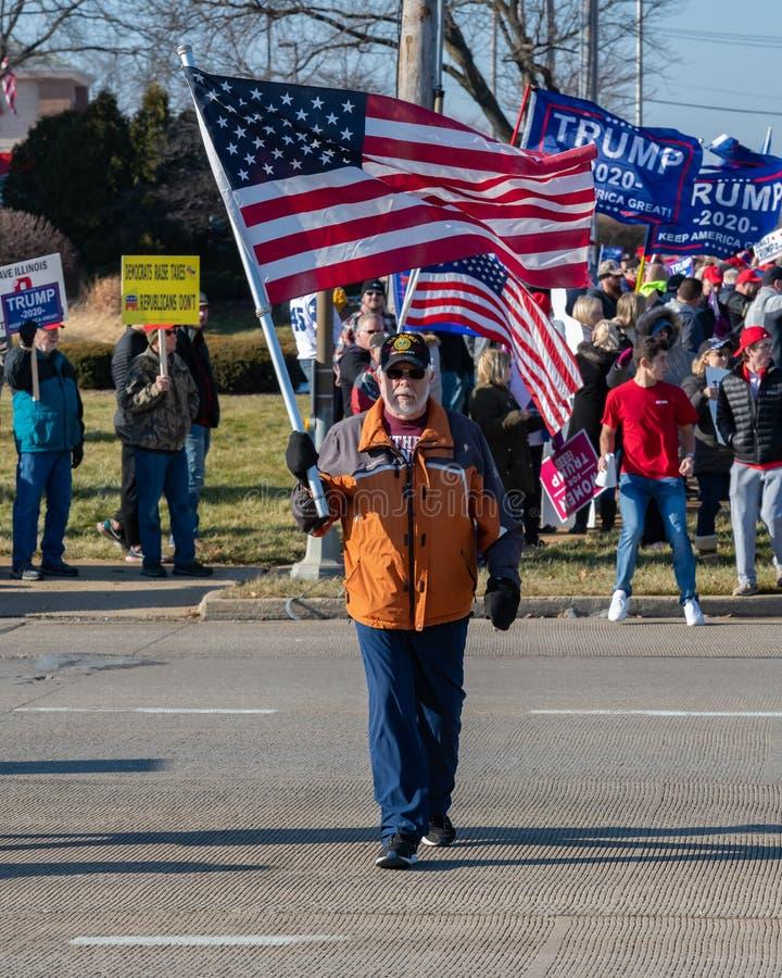 Weteran wojska macha flagą na wiecu wspierającym prezydenta Donalda Trumpa, gdzie były liczne sygnały antyimpeachmentu fotografia royalty free