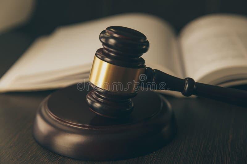 Wetsconcept - Open wetsboek met een houten rechtershamer op lijst in een een rechtszaal of bureau van de wetshandhaving op blauw royalty-vrije stock afbeeldingen