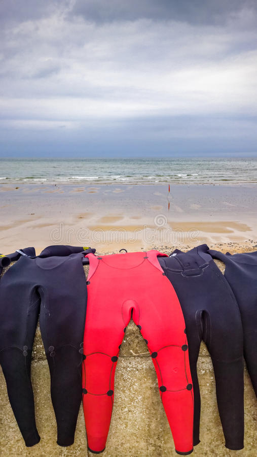 Wetsuits surfants rouges et noirs images libres de droits