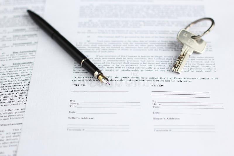 Wettelijk document voor verkoop van onroerende goederen, met vulpen en huissleutels royalty-vrije stock foto's