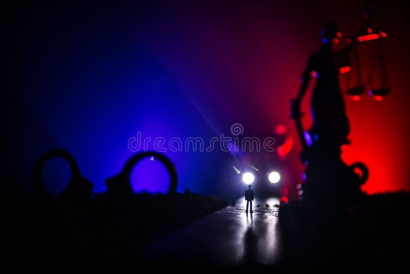 Wettelijk wetsconcept Silhouet van handcuffs met het Standbeeld van Rechtvaardigheid op achtereind met de opvlammende rode en bla stock foto's