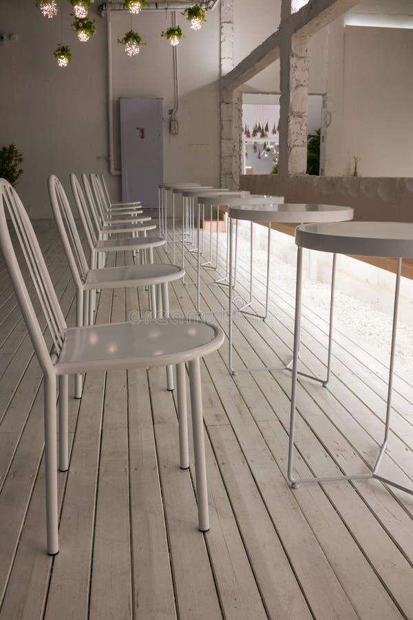 Wewnętrzna dekoracja, biel krzesła i okregów biurka, lampy wieszamy na suficie zdjęcie stock