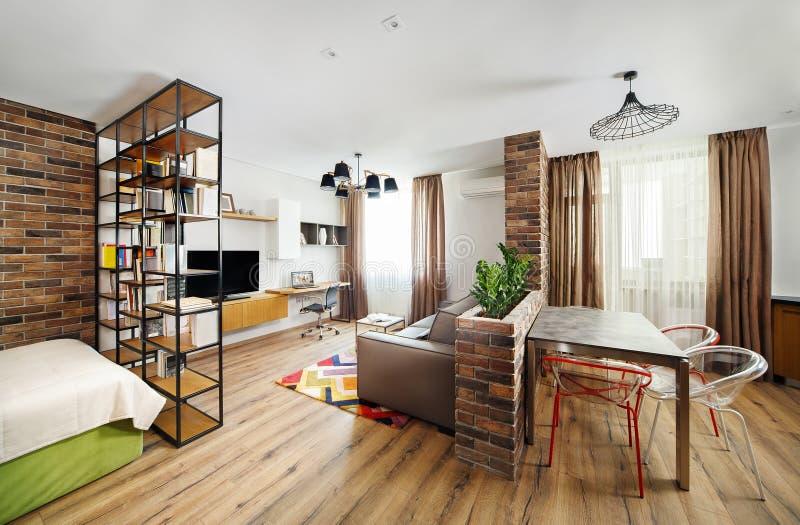 Wewnętrzni pracowniani mieszkania z półka na książki i twarde drzewo podłoga, fotografia stock