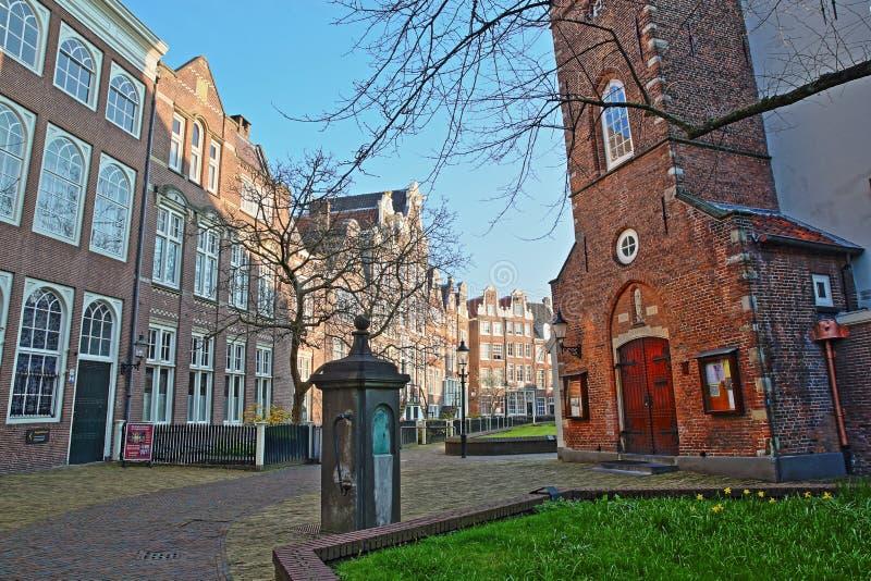 Wewnętrzny podwórze Begijnhof, jeden starzy hofjes w Amsterdam, z Angielskim Reformowanym kościół w przedpolu zdjęcia stock