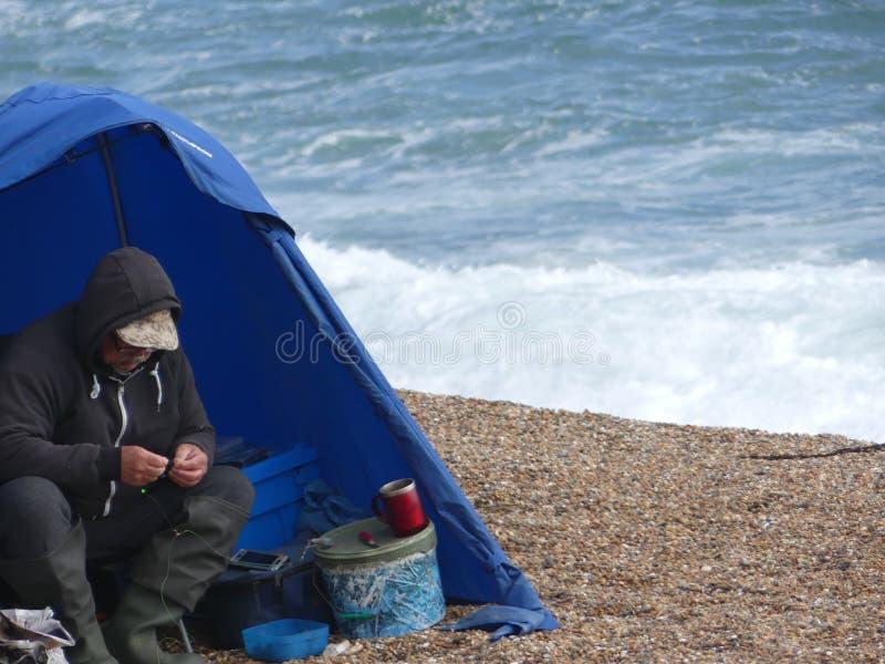 Weymouth England - Juni 20 2018: Manlig fiskare som rullar en cigarr royaltyfri fotografi
