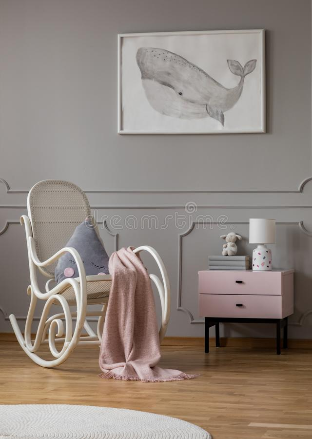Whale on poster in baby room with white rocking chair and pastel pink nightstand with books and lamp royalty free stock photos