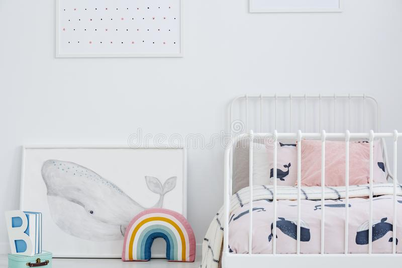 Whale poster and rainbow next to white bed in bright kid`s bedro. Om interior. Real photo stock photo