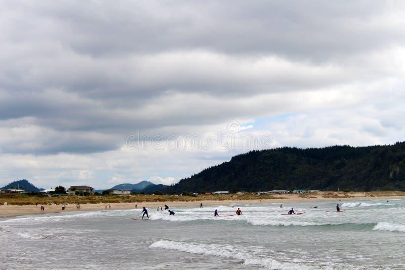 Серферы на пляже Whangamata в Новой Зеландии стоковые изображения