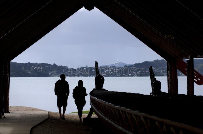 Whare Waka (Canoe house). WAITANGI - OCTOBER 02: Visitors at Whare Waka (Canoe house) with 35 metre Waka (war canoe) on Oct 02 2012 in Waitangi National Reserve stock photo