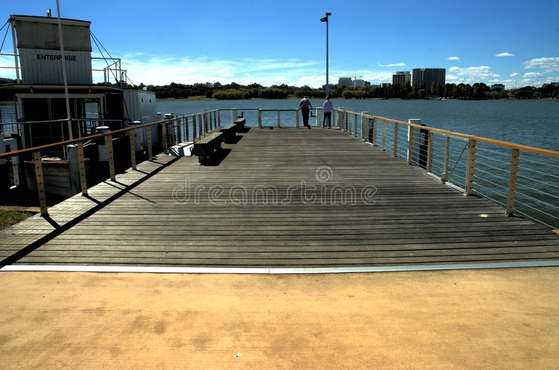 Wharf with a boat and couple royalty free stock photo