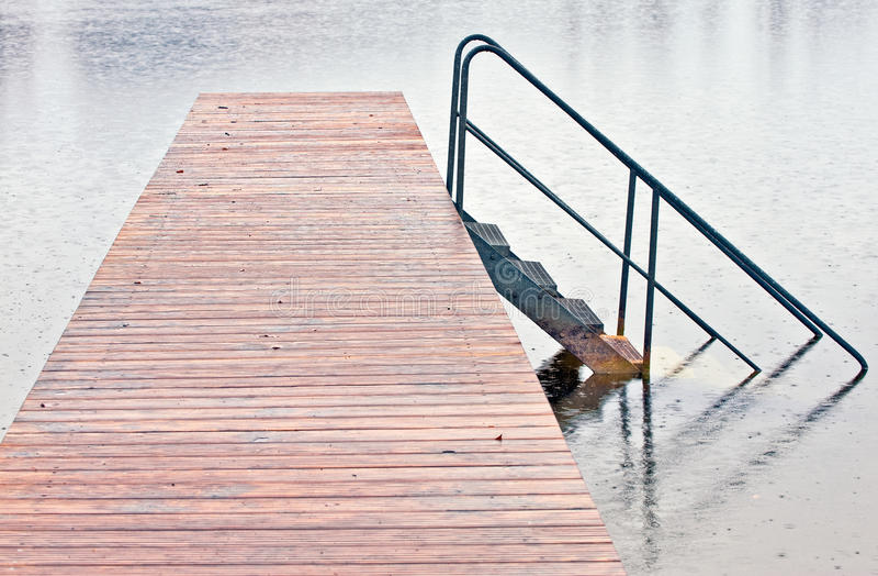 Wharf on lake in rain stock photography