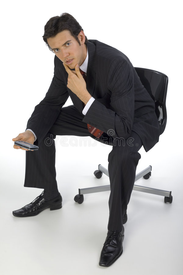 What the... Focused, handsome businessman. Seating on chair with palmtop in hands. White background stock images