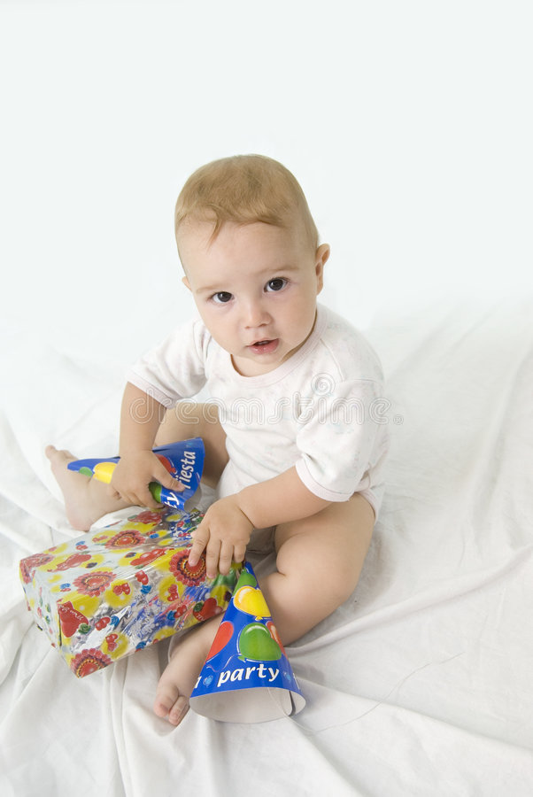 What is it. Cute baby boy looking up and opening his birtday gift stock image