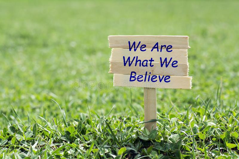 We are what we believe. Wooden sign in grass,blur background stock photos