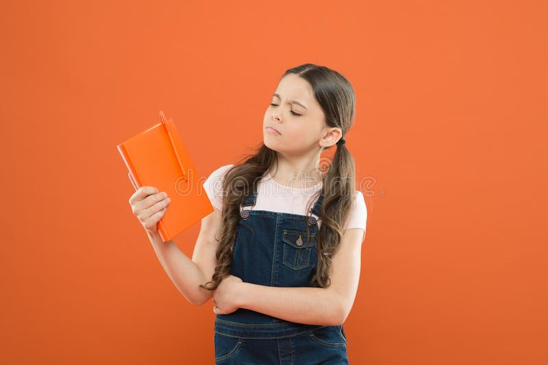 What is this book about. literature lesson. back to school. school girl read book on orange background. poetry and novel royalty free stock photos