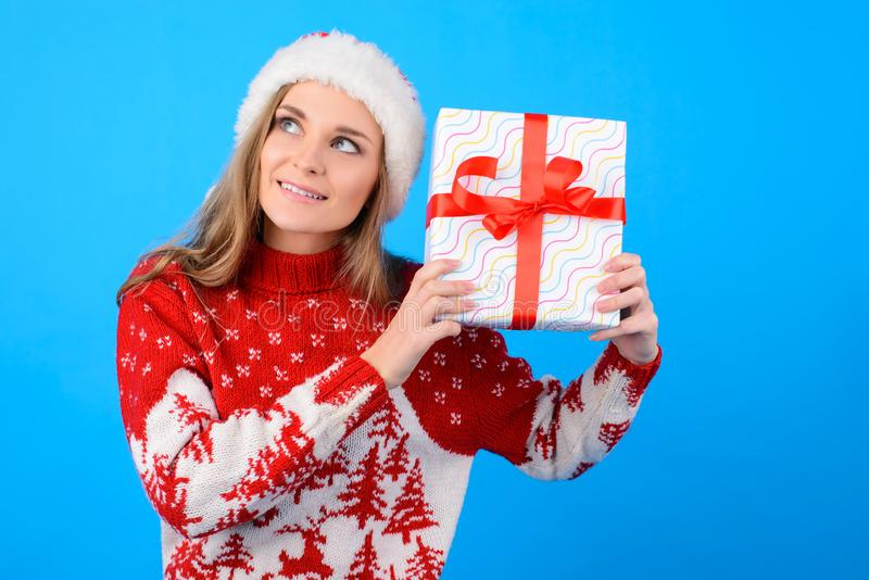 What can be there? Close up portrait of excited joyful happy woman with a present box, isolated on blue background royalty free stock photo