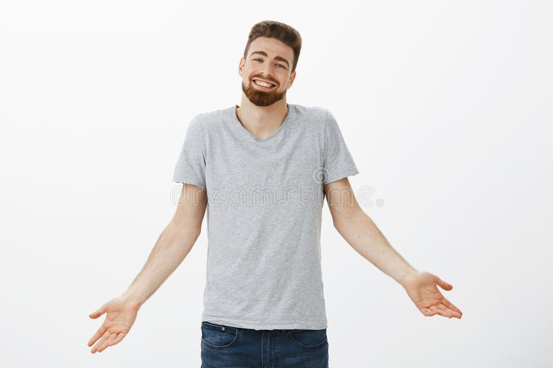 What can i say I am perfect boyfriend. Charismatic charming european guy with beard shrugging with spread arms with. Delighted cute smile receiving compliments stock image