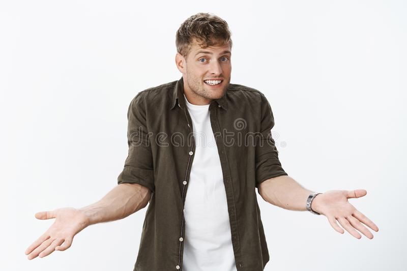 So what chill and relax. Unbothered careless fair-haired guy shrugging with hands raised in confusion and dismay smiling. With apology or sorry look as being stock photos
