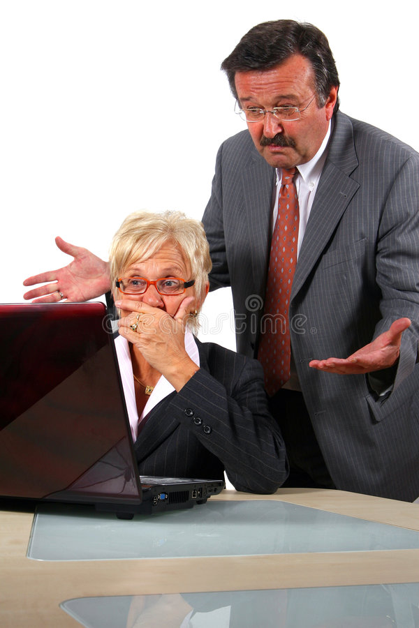 What Did You Do?. A senior businesswoman in her fifties is working on a laptop in an office and seems to be shocked. Her boss behind her is angry. Isolated over royalty free stock photography