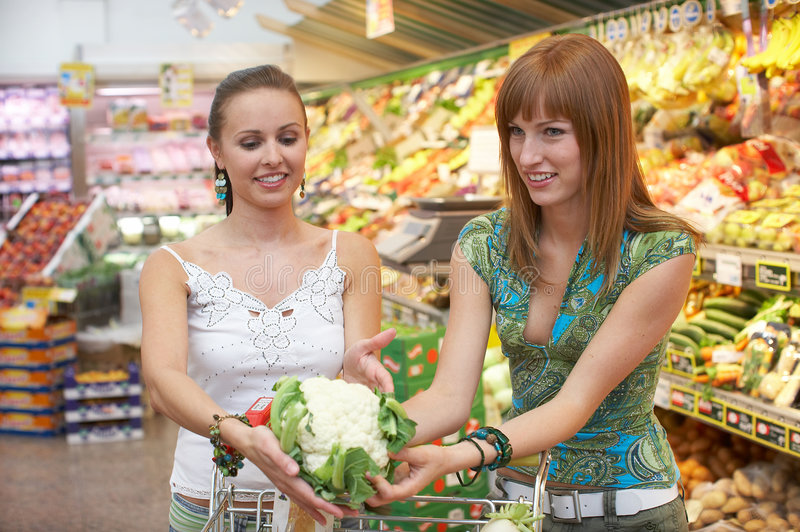 What do we need?. Two friends while shopping royalty free stock image