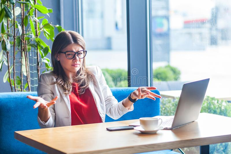 What do you need? Portrait of confused beautiful stylish brunette young woman in glasses sitting and looking at camera and asking royalty free stock photo