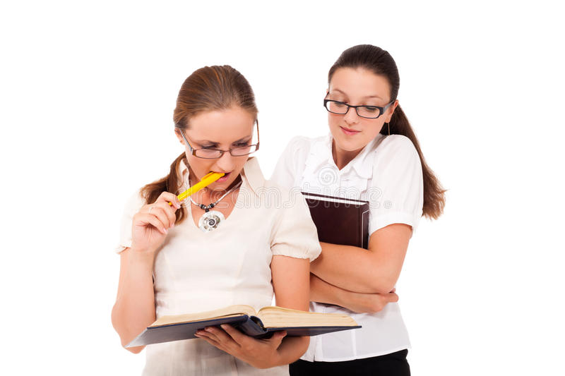 What do you read?. Two student girls are reading the same book stock image