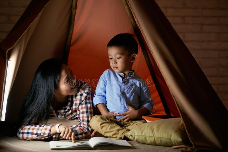 What do you see. Mother asking her son what he sees on a picture in book royalty free stock photo
