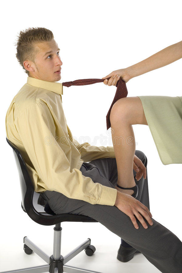 What do you want?. Young, scared businessman, sitting on chair in front of woman in skirt. Woman is pulling his tie. White background royalty free stock image