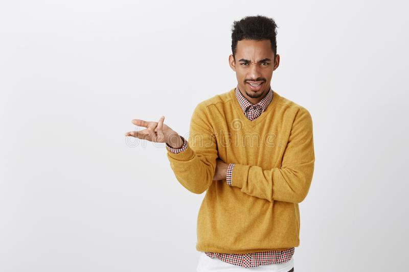 What do you want from me. Portrait of outraged clueless young guy with afro haircut and stylish outfit raising palm and. Shrugging, frowning with displeased stock photos