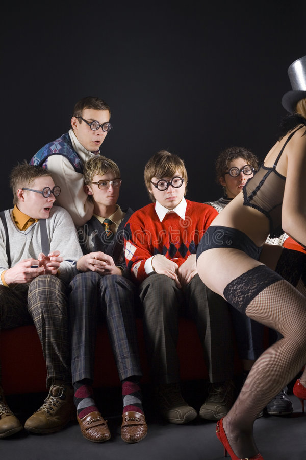 What is she doing?. Five nerdy guys sitting in front of dancing stripteaser. They are looking scared. Front view, whole body stock image