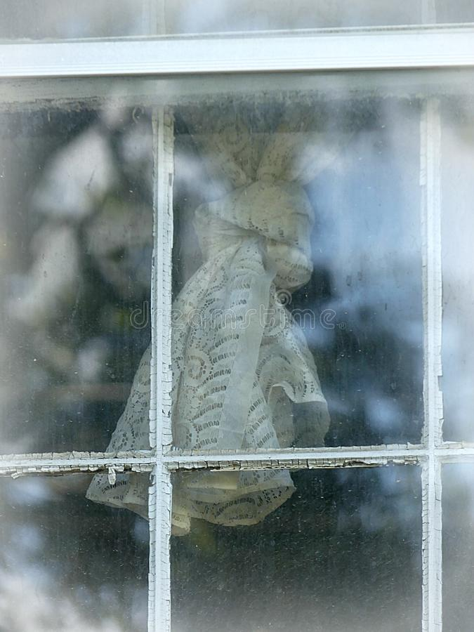 Old Lace Curtain Tied in a Knot behind a Weathered Dirty Window Pane stock image