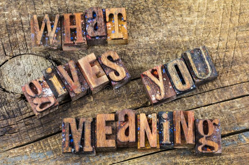What gives you meaning message. What gives you meaning purpose fulfillment in life letterpress wood block letters type old weathered board background retro royalty free stock image