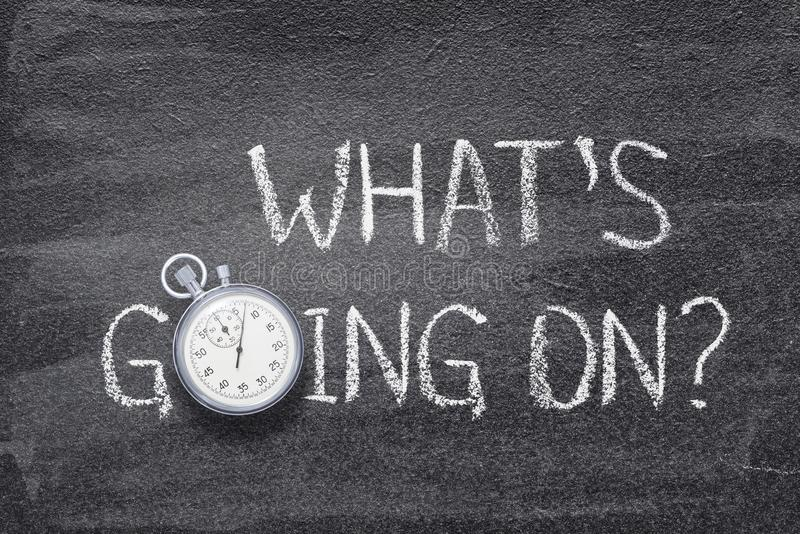 What going on watch. What is going on watch question handwritten on chalkboard with vintage precise stopwatch used instead of O royalty free stock photos