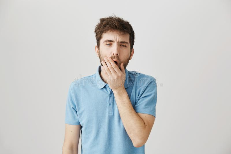 What got you up so early. Studio shot of ordinary mature bearded guy with messy hair yawning, covering mouth with palm. Feeling sleepy and tired, waking up and royalty free stock images