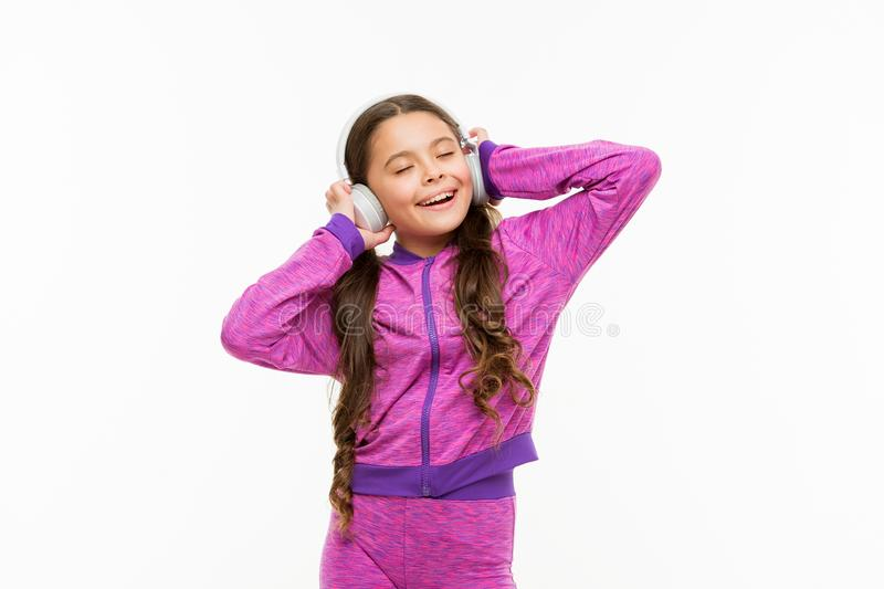 What a great feeling. Athletic little girl relaxing isolated on white. Cute girl child listening to music. Fit small. Girl wearing headphones. Active girl enjoy stock photos