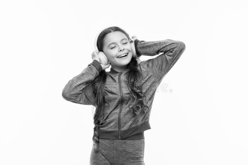 What a great feeling. Athletic little girl relaxing isolated on white. Cute girl child listening to music. Fit small stock photo