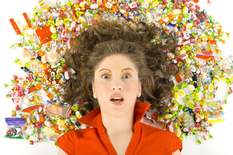 What is happening?. Young, beautiful woman lying on floor among candys. Looking shocked and looking at camera. Front view, white background stock photos