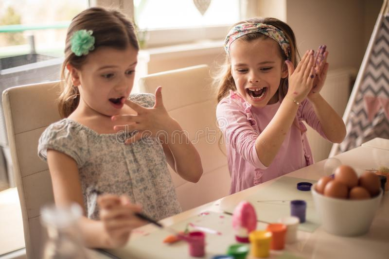 What have I done. ? Little girls coloring Easter egg royalty free stock images