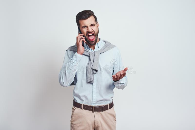 What have you done, oh no! Angry bearded man is screaming while talking with somebody by smartphone. Negative emotions stock image